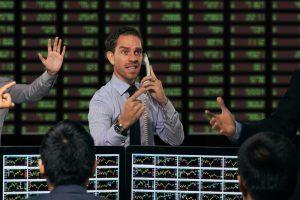 Trader gesturing at stock exchange